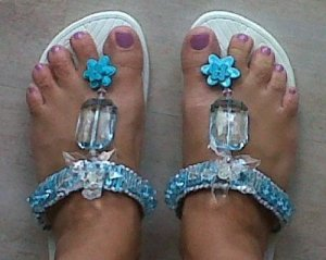 Blue beaded flip flops on woman's feet.