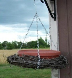 A hanging bird bath made with a grapevine.
