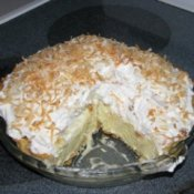 A coconut cream pie with one slice removed.