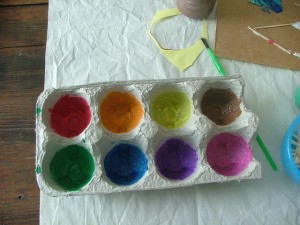An egg carton being used for finger paints.