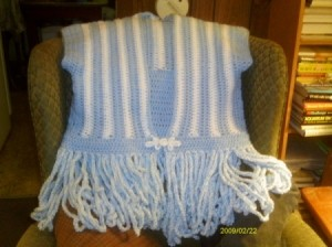 Crocheted Calypso Cardigan, front side displayed on a chair.