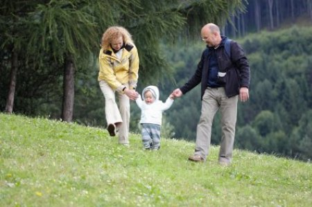 Mother and Father Helping Child with First Steps