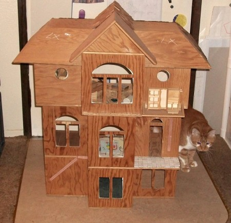 Front view of unfinished plywood doll house.