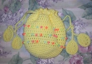 Crochet beaded Easter bag in yellow with pastel beads and egg shapes on ends of drawstrings.