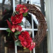 A red silk flower and grapevine wreath