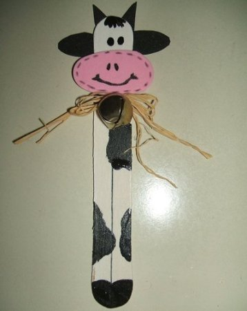 A whimsical cow bookmark in black and white and pink with a rustic bow..