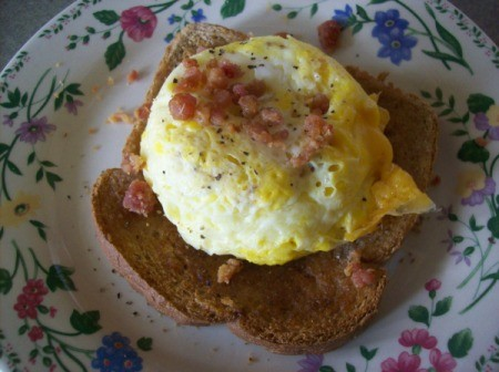 Quick Cheesy Egg On Toast on a plate with bacon bits as a garnish.