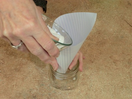 pouring baking soda into jar using a paper funnel