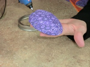 Applying hot glue to pincushion.