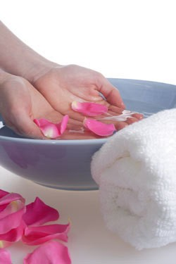 Woman Dipping Her Hands in Water With Rose Petals