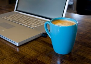 Cup of Coffee Next to Laptop