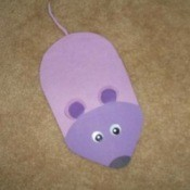 A purple foam mouse shaped mouse pad.