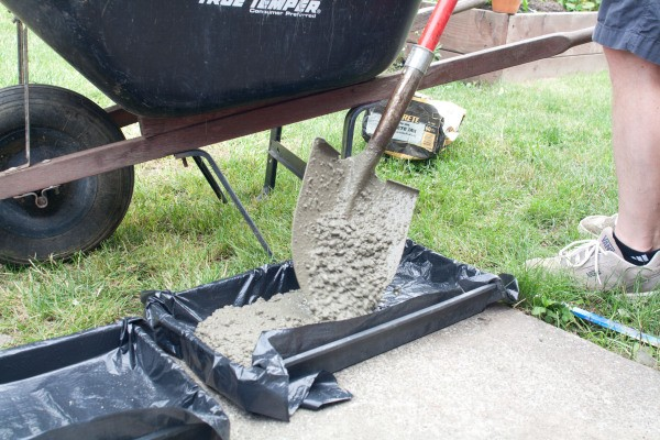 Pouring Concrete into Mold with Shovel