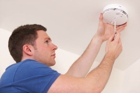 Man Servicing Smoke Alarm