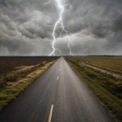 A roadway with storm clouds and lightning in the distance