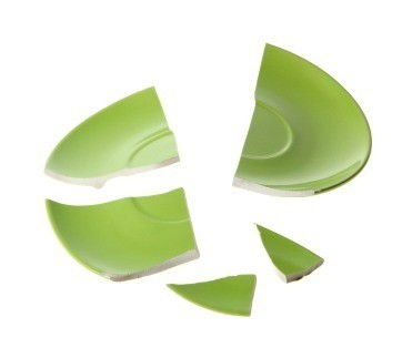 A broken green dish in several pieces