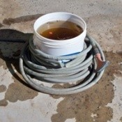 A hose wrapped around a plastic bucket.