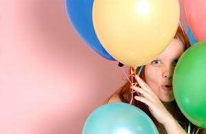 A girl looking through birthday balloons.
