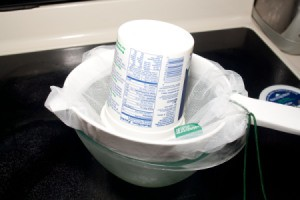 Straining yogurt through a mesh bag and strainer.