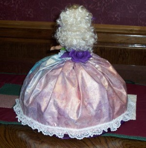 View of back of doll in pink dress.