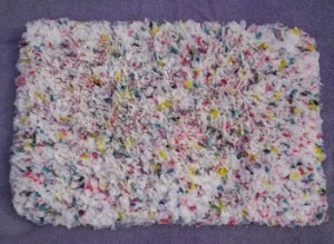 Multicolored hooked rug made with shopping bags.