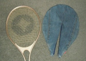 Racket cover next to tennis racket.