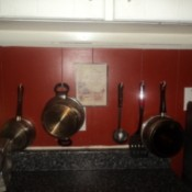 Pots and utensils hanging on kitchen wall.