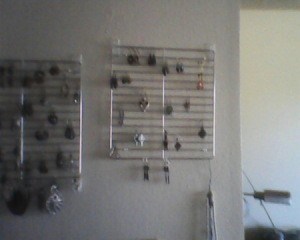 Jewelry hanging from racks, mounted on wall.