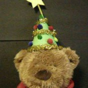 Little Christmas tree hat on stuffed bear.