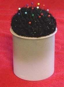 Pincushion made from frosting tub and ball of yarn.
