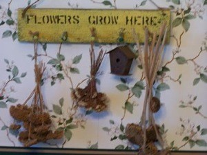 Finished project with dried flowers hanging from pegs.