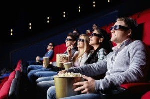 Audience in theater wearing 3D glasses and eating popcorn.