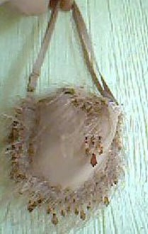 Purse made from an underwire bra with decorative edging.