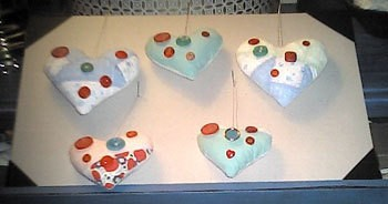 Pieced heart shaped ornaments decorated with buttons.