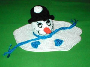 Snowman's head on a melted puddle of white crochet.