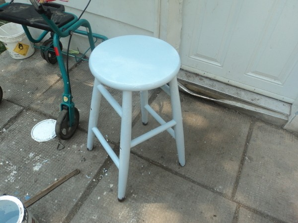 A wooden stool painted blue.