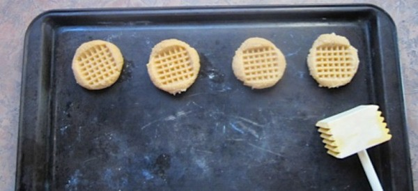 Cookies on baking sheet and tenderizer.