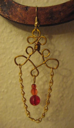Brass tone wire and chain link earring with red beads.