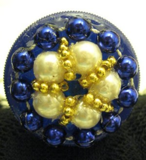 Blue, pearl, and gold beaded jar lid.