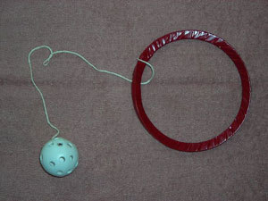 Ring for around the leg with ball attached for children's game.