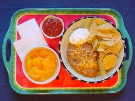 Serving tray with pasta bowl of bean dip, chips, sour cream, and a side of salsa.