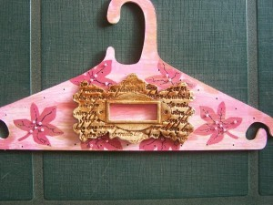 Embellishment glued on front of hanger.