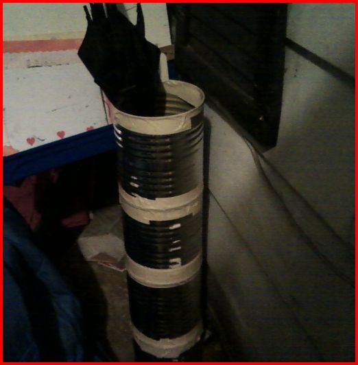 Large tin cans taped together to make an umbrella stand.