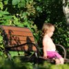 Little girl sitting quietly on a bench, in the garden.