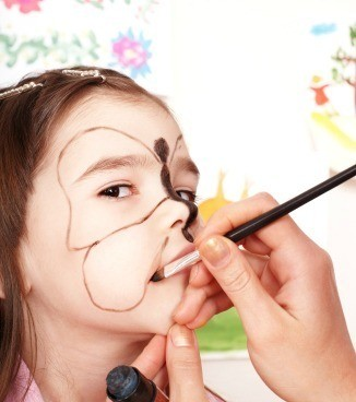 A girl at a harvest festival having her face painted.