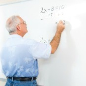 Photo of a teacher writing on a dry erase board with his sleeves rolled up.