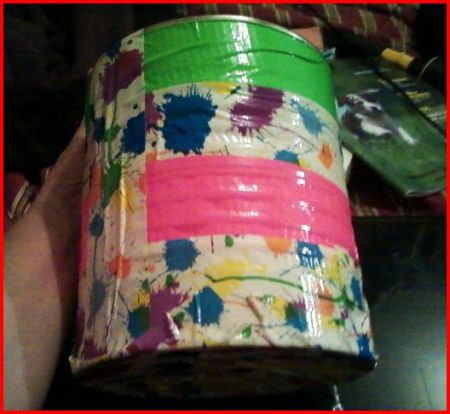 Can covered with floral and bright pink and green duct tape.