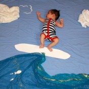 Baby lying on a sheet with other sheets and paper cutouts arrange to make it look as though he is surfing.