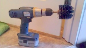 Toilet brush mounted on cordless drill.