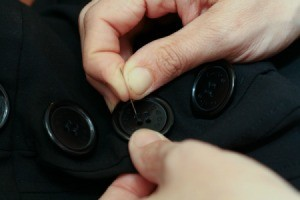 Closeup of Sewing Buttons On Clothing